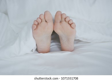 Crop shot of woman lying under cozy white blanket in bed sticking out feet while sleeping and relaxing.