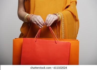 crop shot of woman in sari holding shopping bags