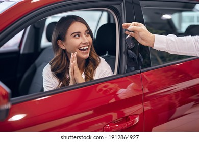 Crop showroom agent giving key to amazed female client sitting in car and clapping hands