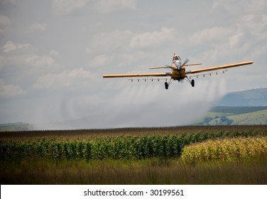 crop sprayer in action over corn field