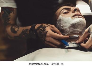 Crop stylish applying foam on customer's cheeks for shaving while working in barbershop.