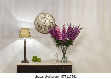 Crop of stylish and lighting corridor with wooden commode, retro watch over. Violet flowers in vase and lamp on commode flowers pot with cactus. Little ceramic owls.