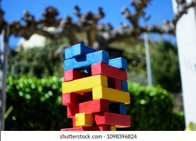 Crop of top of colored wooden bricks of jenga game against defocused leafless tree and hedge.