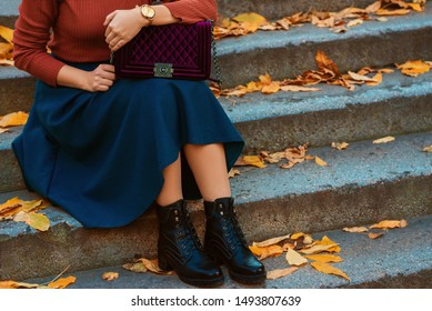 Crop of trendy autumn woman`s fashion outfit: purple velour quilted bag, golden wrist watch, blue midi skirt, black chunky ankle boots. Copy, empty space for text