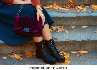Crop of trendy autumn woman`s fashion outfit: purple velour quilted bag, blue midi skirt, black chunky ankle boots. Copy, empty space for text