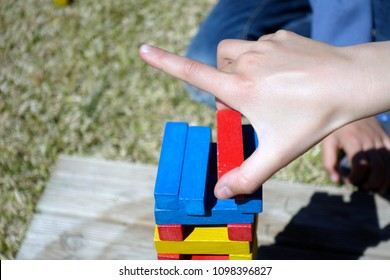 Crop of unrecognizable child putting red wooden brick on top of jenga tower while entertaining outdoors on summer day.