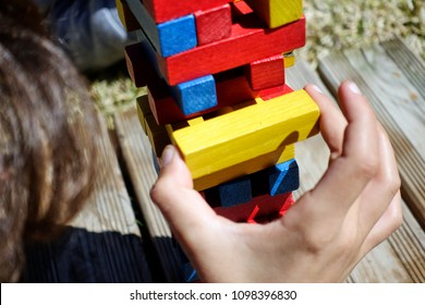Crop of unrecognizable kid playing jenga. Kid holding yellow brick in two fingers.