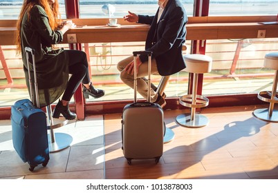 Crop unrecognizable man and woman with suitcases drinking coffee in cafe of airport.