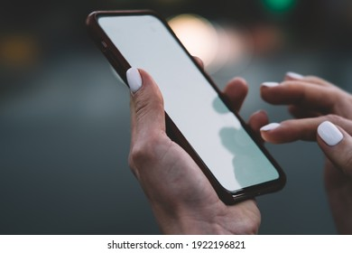 Crop unrecognizable woman with manicured hands messaging in social media on modern mobile phone with empty screen in city on blurred background
