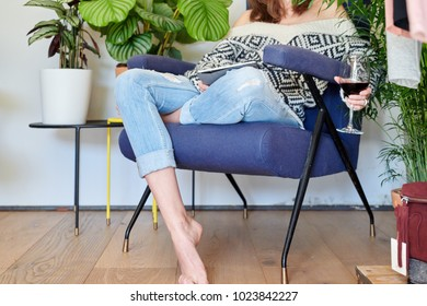 Crop view of barefoot model in denim and sweater cuddling with wineglass using tablet.