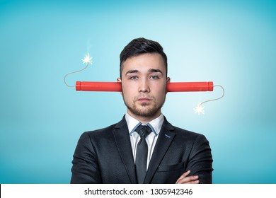 Crop view of a businessman, arms folded, burning dynamite sticks up his ears, on a light-blue background. Have hard day. Work your brain out. Blow your mind.