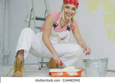 Crop view of happy young attractive woman in white overalls and red bandana sitting on hunkers at bucket and dipping roller in tray with pastel yellow wall paint looking at camera and smiling.