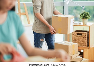 Crop view of man and woman carrying large packed carton boxes on moving day with blurred foreground