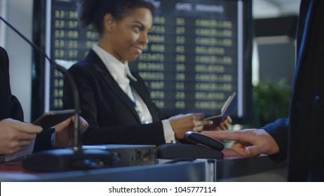Crop view of people passing through registration counter with multiracial receptionists in airport having biometric control.