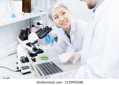 Crop view of smiling female microbiologist standing at eyepiece of microscope with samples of green vegetables looking at colleague typing results of analysis on laptop