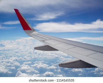 crop view of a white silver metallic airplane wing from passenger window as the machine flying high under bright blue sky on a cloudy day