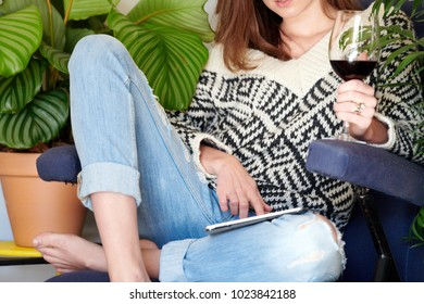 Crop view of woman in cozy sweater browsing tablet while drinking red wine in armchair.