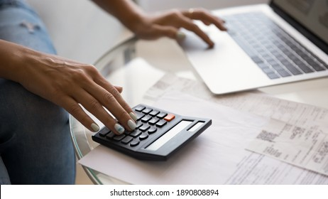 Crop wide banner view of woman sit at desk pay bills taxes on laptop online, manage home finances. Female busy calculating household expenses expenditures on calculator, make payment on computer.