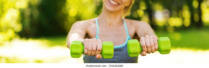 Crop of woman doing fit activity and training with dumbells,outside at summer park. Fitness, sport and healthy lifestyle long banner