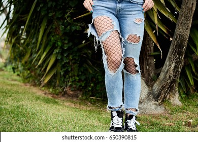 Crop of woman in extremely ripped jeans and fishnet tights under them on green grass.
