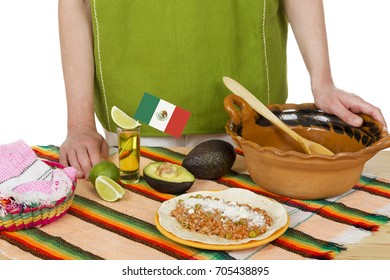 Crop woman in green national dress standing at table with Mexican food and tequila shot.