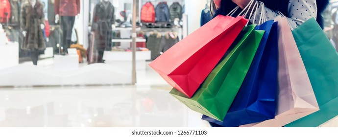 Crop woman holding colorful heap of paper bags on background of shopping center. Woman shopping in mall, copy space. Concept of spending money and consumerism. Female desire to buy more things.