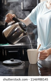 Crop woman holding kettle and filling mug with hot water while brewing drink in modern kitchen