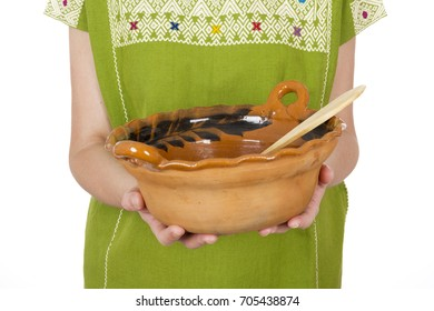 Crop woman in traditional Mexican clothing holding clay painted dish on white background.