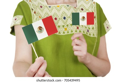 Crop woman wearing Mexican traditional clothing and holding small Mexican flags on white background.