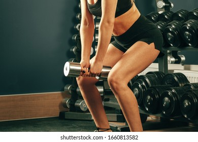 Crop of woman wearing sportswear  making exercise with dumbbells in gym