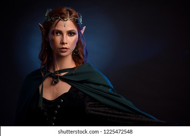 Crop of young and beautiful woman in green cloak posing at camera. Charming queen of elves in silver tiara and red hair gesturing by her left hand. Isolated of girl on dark blue studio background.