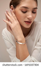 Crop of young female model with perfect makeup presenting minimalistic silver bracelet. Portrait of woman posing in studio, isolated on gray background. Concept of jewelery.