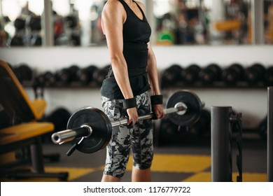 Crop of young and strong woman with athletic body doing exercises with barbell in gym. Brunette woman with short haircut, wearing in stylish sports wear, doing workout alone. Concept of fit.