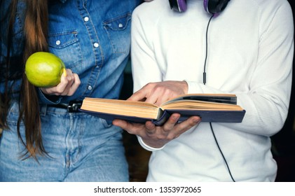 Croped view of two studens holding apple and book while preparing to the lesson