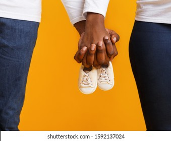Cropped of afro couple holding baby boots together over yellow studio background, baby is coming