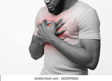 Cropped of afro man suffering from acid reflux or heartburn, symptomatic indigestion or gastritis disease, white background