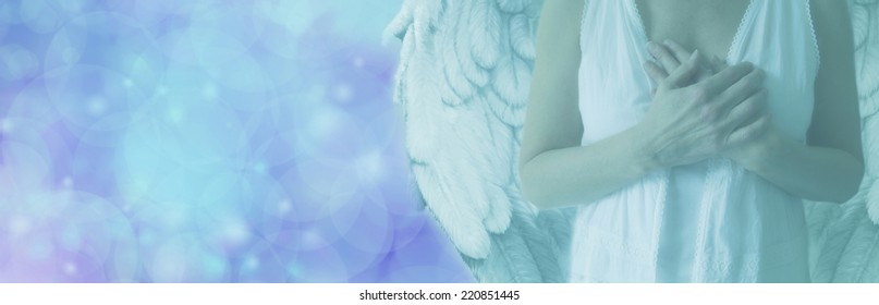 Cropped Angel showing torso in white robes with hands held over heart on a misty blue bokeh background with copy space on left hand side