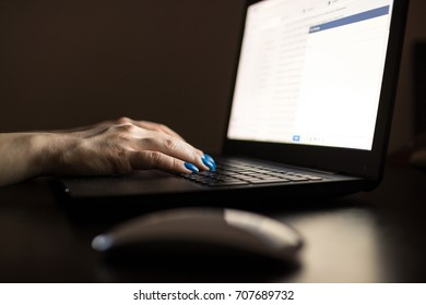 Cropped angled view image of a female hand using computer at office table in the dark. Late night browsing