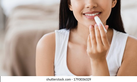 Cropped of asian woman using lipbalm, bedroom interior, panorama with empty space