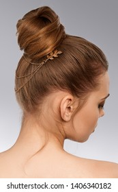 Cropped back view closeup shot of lady with massive bun, adorned with golden hairpin with long cascade chains and inserts in view of twig with leafs. The girl is turning head on the gray background.