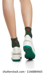 Cropped back view of lean woman's legs in green ankle high socks with red hearts and thick-soled running shoes, isolated against a white background. Trendy hosiery and footwear for ladies and girls.