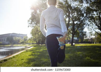 Cropped back view of unrecognizable woman runner doing warm up routine outdoors before running, stretching quadricep muscles on grass in park. Athletic girl preparing legs for cardio workout