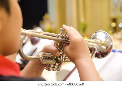 Cropped and backview image, boy playing trumpet with an orchestra on the stage