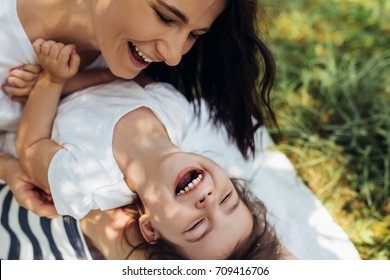Cropped beautiful happy mother and her little smiling daughter outdoors. Cute mom and her child playing in the park together. Close-up portrait of happy family. Happy Mother's Day. Motherhood.