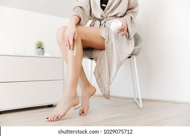 Cropped beauty portrait of slim woman with soft healthy skin applying body cream on her legs at home