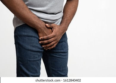 Cropped of black man holding his groin over white background, copy space