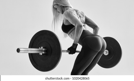 Cropped black and white conceptual inspiration lifestyle photo of female fitness model workout Perfect trained body chest booty legs arms chest Confident blonde woman weight lifting workout at gym