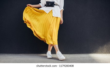 Cropped body shot of attractive woman in beautiful yellow skirt. Caucasian female fashion model standing over gray wall background outdoor with copy space.