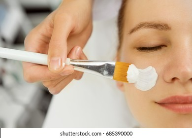 Cropped close up of a beautician applying facial mask on a young female face client service treatment therapy therapist dermatology cosmetology refreshing pampering wellness spa recreation skincare