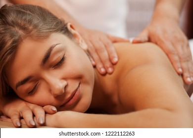 Cropped close up of a beautiful happy healthy young woman smiling with her eyes closed, while professional masseur massaging her back and shoulder, copy space. Medical treatment, stress relief concept